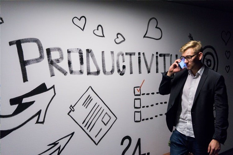 business man standing in front of a board that has Productivity written on it